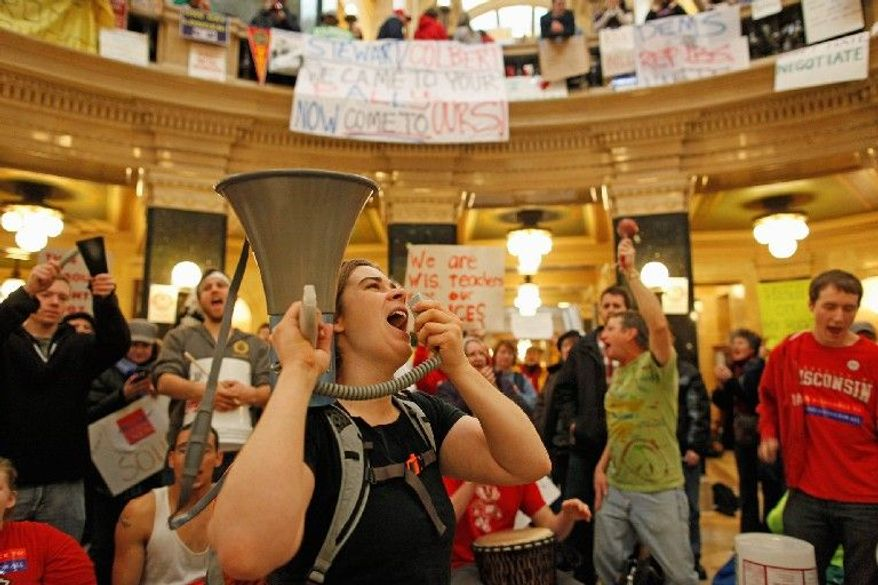 Protesters bang drums and shout slogans at the state Capitol on Monday in Madison, Wis. They were there to oppose Wisconsin Gov. Scott Walker's proposed legislation to curtail collective-bargaining rights for most state employees. (Associated Press)