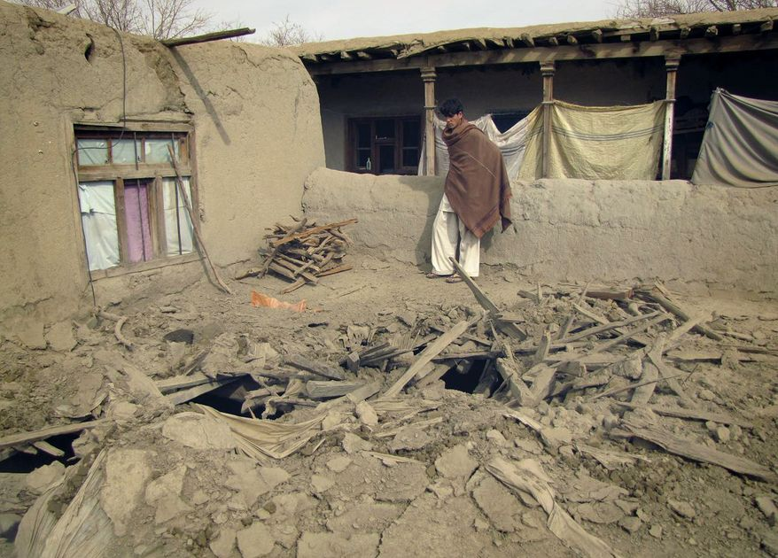 An Afghan youth looks at the damage caused during a NATO raid in the Khogyani district of Nangarhar province, east of Kabul, Afghanistan, on Monday, Feb. 21, 2011. The NATO coalition says it is investigating the accidental death of Afghan civilians in Nangarhar province along the Pakistan border. (AP Photo)