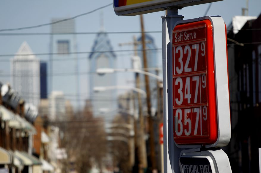 **FILE** Prices for gas are seen Wednesday posted in view of the city skyline in Philadelphia. (Associated Press)