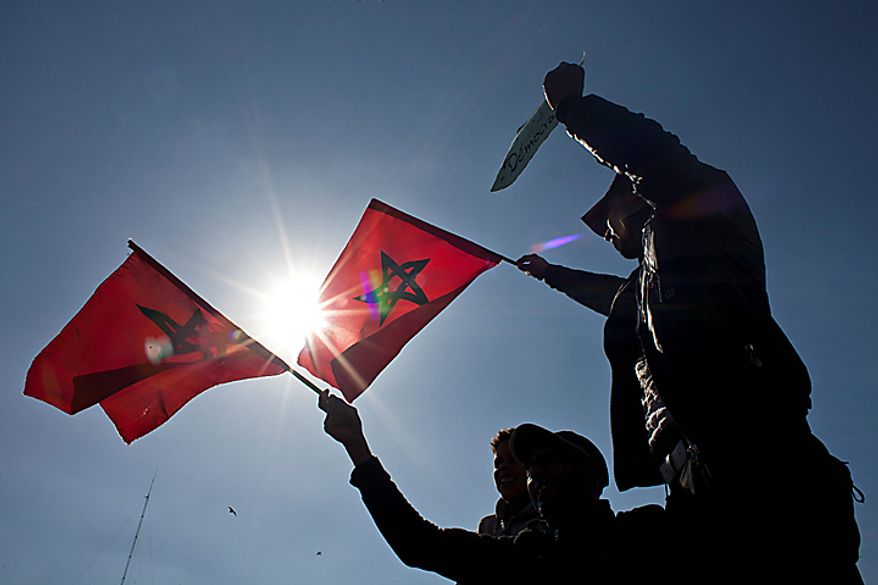 Protesters hold the Moroccan flag  during a demonstration in Casablanca, Morocco, on Sunday, Feb. 20, 2011. Thousands of people marched in cities across Morocco on Sunday, demanding a new constitution to bring more democracy in the North African kingdom amid the wave of Arab world upheaval. (AP Photo/Thibault Camus)