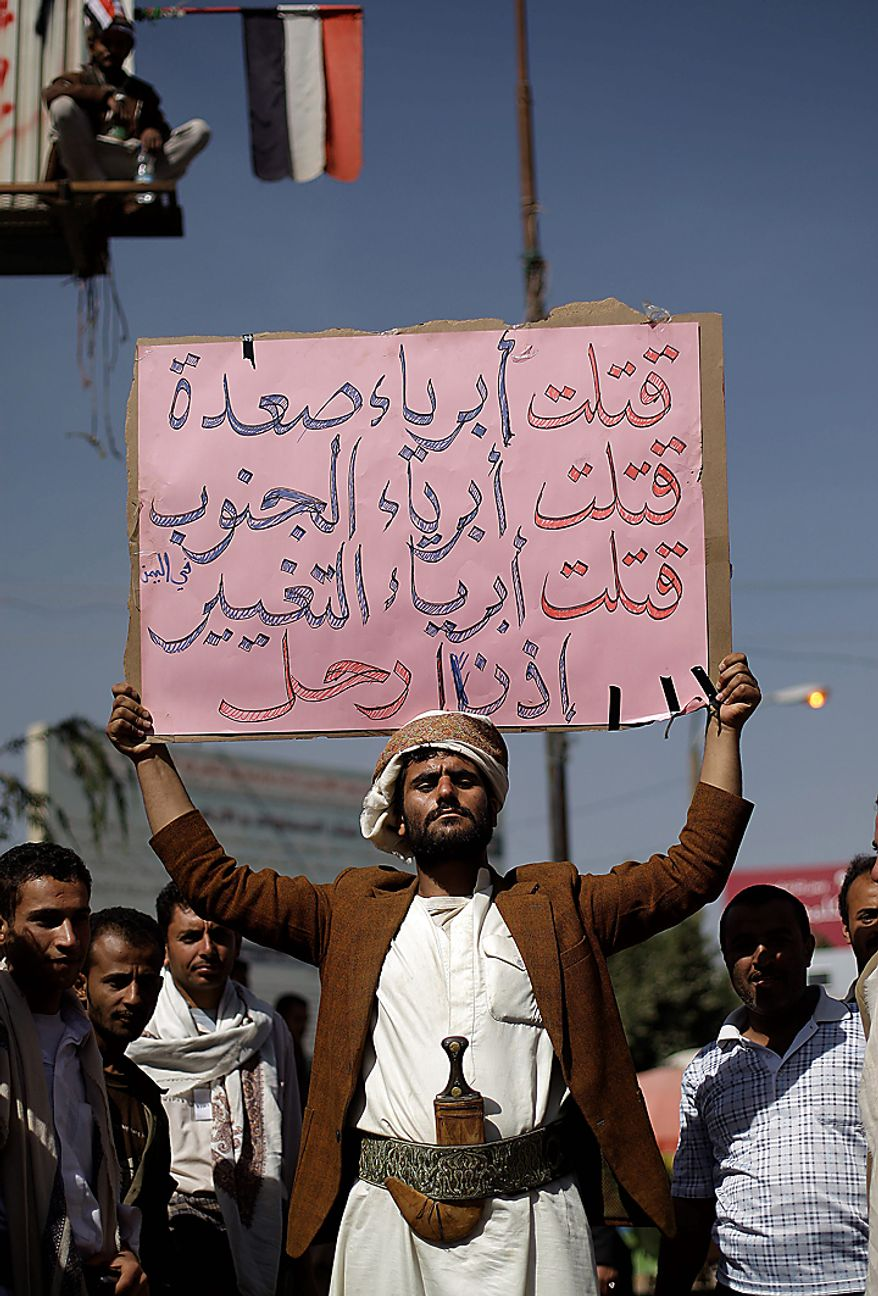 "An anti-government demonstrator holds a banner that reads in Arabic, ""You killed innocent people in Saada, you killed the innocent people of the South, you killed the innocent people of the change, so leave,"" during a demonstration demanding the resignation of Yemeni President Ali Abdullah Saleh in Sanaa, Yemen, on Monday, Feb. 21, 2011. Mr. Saleh rejected demands that he step down and said Monday that the widespread demonstrations against his regime were unacceptable acts of provocation, though he renewed calls for talks with the protesters. (AP Photo/Muhammed Muheisen)"