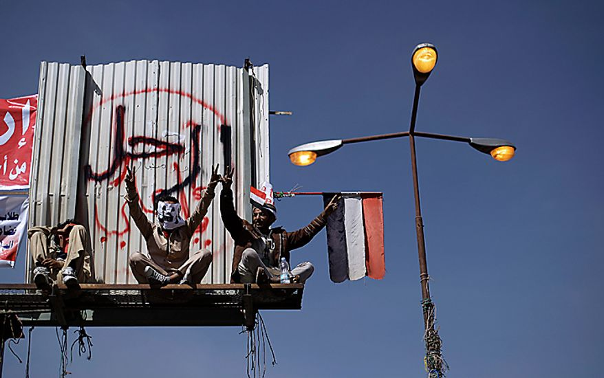 "Yemeni anti-government demonstrators gesture while sitting on a billboard that says ""Leave"" in Arabic during a demonstration demanding the resignation of President Ali Abdullah Saleh in Sanaa, Yemen, on Monday, Feb. 21, 2011. Mr. Saleh rejected demands that he step down and said Monday that the widespread demonstrations against his regime were unacceptable acts of provocation, though he renewed calls for talks with the protesters. After a week and a half of marches that have left nine dead, Mr. Saleh told a news conference that he had ordered the army to fire at demonstrators ""only in case of self-defense."" (AP Photo/Muhammed Muheisen)"