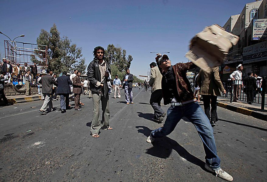 "An anti-government demonstrator hurls a stone at supporters (not pictured) of the Yemeni government during clashes in Sanaa, Yemen, on Saturday, Feb. 19, 2011.  Hundreds of Yemenis began demonstrating early in the day outside the university in Sanaa demanding the ouster of the country's longtime ruler as they marched toward the Justice Ministry. ""The people want the ouster of the regime,"" they chanted. (AP Photo/Muhammed Muheisen)"