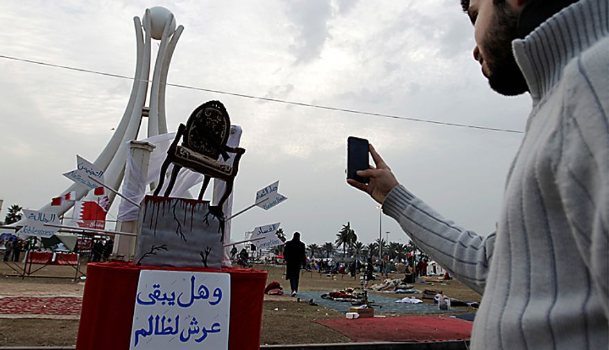 "A Bahraini anti-government protester takes a picture with his cell phone of a chair with a sign in Arabic below it reading, ""And does the throne of the oppressor stay?"" at Pearl Square in Manama, Bahrain, on Monday, Feb. 21, 2011. (AP Photo/Hassan Ammar)"