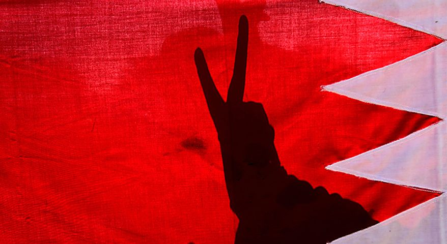 A Bahraini anti-government protester flashes a victory sign behind a Bahraini flag at the Pearl Square in Manama, Bahrain, on Sunday, Feb. 20, 2011. Bahrain's opposition leaders gathered Sunday to examine offers for talks by Bahrain's rulers after nearly a week of protests and deadly clashes that have sharply divided the strategic Gulf nation. (AP Photo/Hassan Ammar)