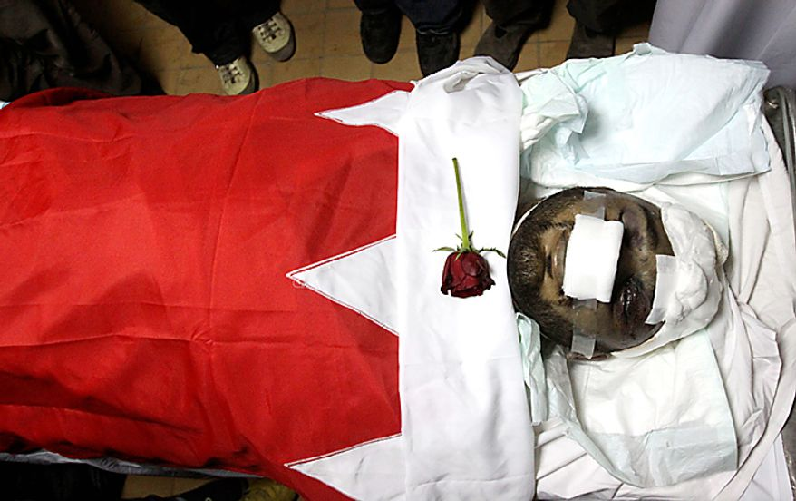 The body of Redha Buhameed, who was killed on Friday, Feb. 18, 2011, allegedly by the Bahraini army, lies in a hospital in Manama, Bahrain, on Monday. A group of protesters called for the ouster of Bahrain's entire ruling monarchy as part of sweeping demands to call off a weeklong uprising in the tiny, but strategically important, Gulf nation. Tensions are still high in Bahrain after seesaw battles that saw riot police open fire on protesters trying to reclaim landmark Pearl Square last week. At least eight people have been killed and hundreds injured in the clashes since the unrest spilling across the Arab world reached the Gulf. (AP Photo/Hasan Jamali)
