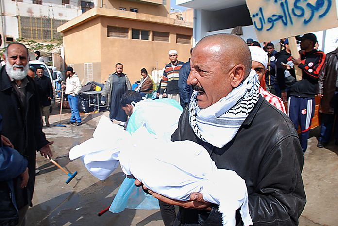 """A Libyan carries away partial remains of a man's body at Al-Jalaa Hospital in Benghazi, Libya on Monday, Feb. 21, 2011. Protesters celebrated in the streets of Benghazi on Monday, claiming control of the country's second-largest city after bloody fighting, and anti-government unrest spread to the capital, with clashes in Tripoli's main square for the first time. Writing on placard in Arabic reads """"Ramzi Al-Hawat""""; the reason for the name is not known. (AP Photo/Alaguri)"""