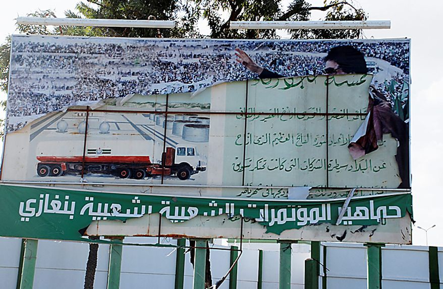 """This photograph, obtained by the Associated Press outside Libya and taken by a person not employed by AP, shows a scene from recent days' unrest in Benghazi, Libya. Writing in Arabic in white on green at the base of torn government banner showing Libyan leader Moammar Gadhafi reads, """"The popular masses of the popular conferences in Benghazi."""" (AP Photo)"""