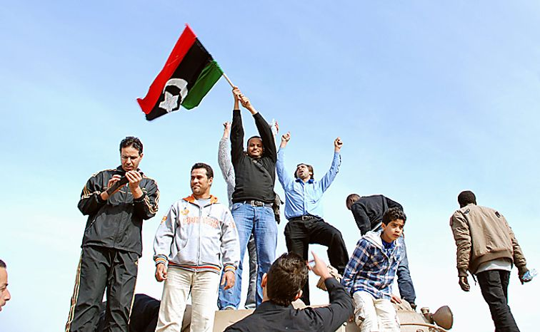 Residents stand on a tank holding a pre-Gadhafi-era national flag inside a security forces compound in Benghazi, Libya, on Monday, Feb. 21, 2011. Libyan protesters celebrated in the streets of Benghazi on Monday, claiming control of the country's second-largest city after bloody fighting, and anti-government unrest spread to the capital, with clashes in Tripoli's main square for the first time. (AP Photo/Alaguri)