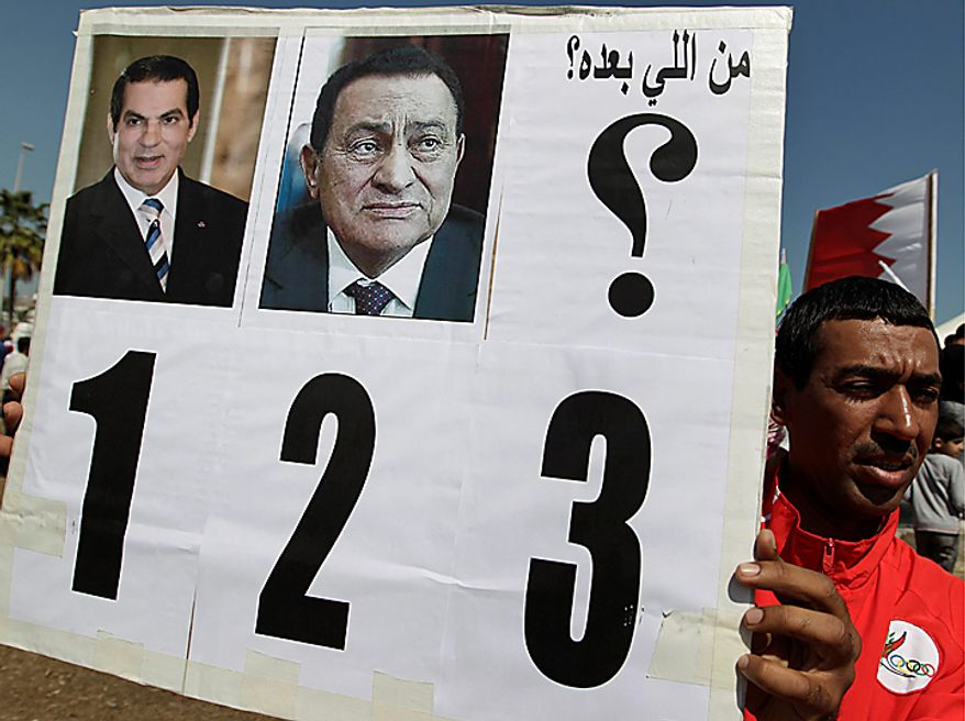 "A Bahraini anti-government protester holds up a banner with pictures of former Tunisian president Zine El Abidine Ben Ali, left, and former Egyptian president Hosni Mubarak, center, and says in Arabic ""who is next?"" at the Pearl roundabout in Manama, Bahrain, Saturday, Feb. 19, 2011. Bahrain's opposition leaders gathered Sunday to examine offers for talks by Bahrain's rulers after nearly a week of protests and deadly clashes that have sharply divided the strategic Gulf nation.(AP Photo/Hassan Ammar)"