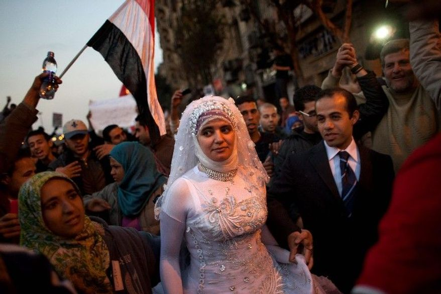 An Egyptian married couple are surrounded by anti-Mubarak protesters in Tahrir Square in Cairo on Feb. 8. Many Egyptians say that financial freedom that allows them to marry is a component of the new democratic country they hope will emerge with President Hosni Mubarak's ouster. (Associated Press)