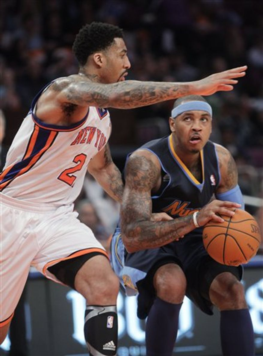 """In this Dec. 12, 2010, photo, Denver Nuggets' Carmelo Anthony, right, works against New York Knicks' Wilson Chandler during an NBA basketball game in New York. Anthony acknowledged after his 38-point performance in Milwaukee on Wednesday night, Feb. 16, that he has no idea what will happen as trade talks surely intensify this All-Star weekend. """"I'm waiting to see just like (everybody else),"""" he said. (AP Photo/Seth Wenig)"""
