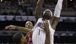 Toronto Raptors' Ed Davis (32) dunks on Charlotte Bobcats' Gerald Wallace (3) and Nazr Mohammed (13) in the first half of an NBA basketball game in Charlotte, N.C., Tuesday, Feb. 22, 2011. (AP Photo/Chuck Burton)