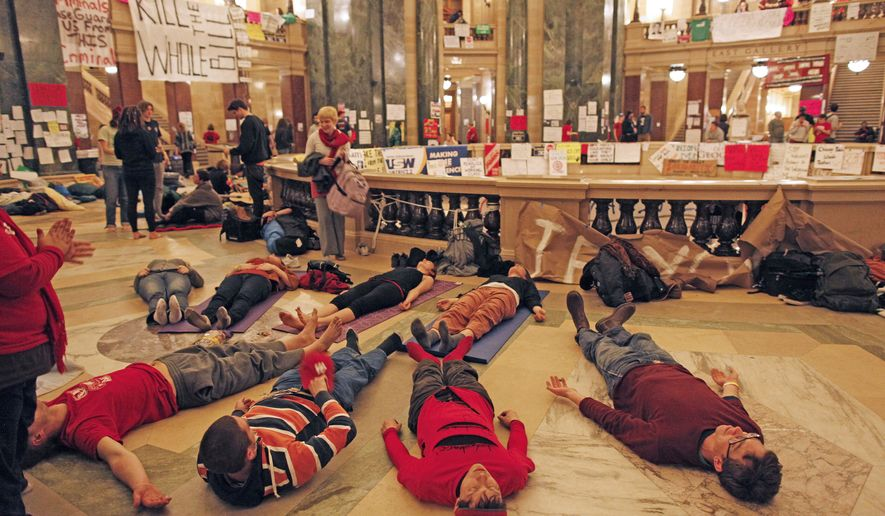 Protesters do yoga inside the state Capitol on Tuesday, Feb. 22, 2011, in Madison, Wis. Opponents to Gov. Scott Walker's bill to eliminate collective bargaining rights for many state workers are taking part in their eighth day of demonstrations. (AP Photo/Jeffrey Phelps)