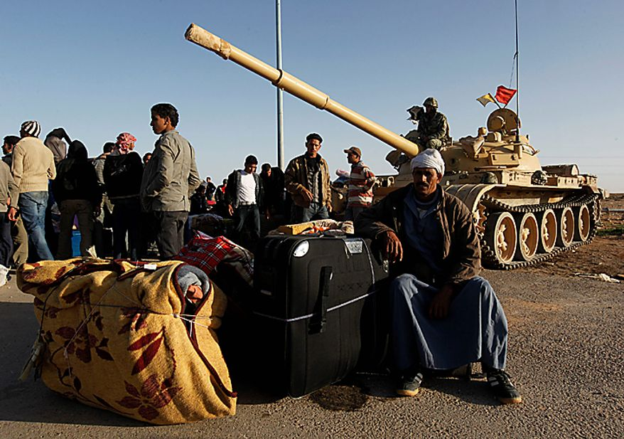 Egyptians who fled from Libya through the Salloum land port gate wait with their belongings next to an Egyptian armored vehicle at the Egyptian-Libyan border, in Salloum, Egypt, Tuesday, Feb. 22, 2011. An estimated 5,000 Egyptians have returned home from Libya by land, and about 10,000 more are waiting to cross the Libya-Egypt border, an Egyptian security official said Tuesday. (AP Photo/Hussein Malla)