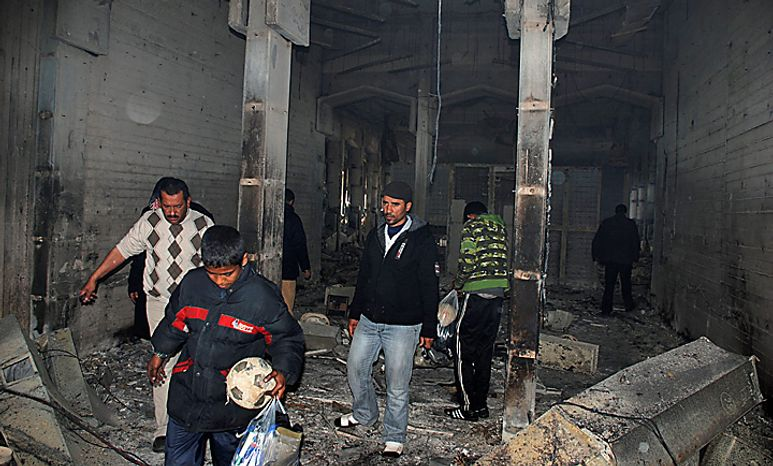 Residents are seen walking inside an unidentified burned building in Benghazi, Libya, on Monday, Feb. 21, 2011. Libyan protesters celebrated in the streets of Benghazi on Monday, claiming control of the country's second largest city after bloody fighting, and anti-government unrest spread to the capital with clashes in Tripoli's main square for the