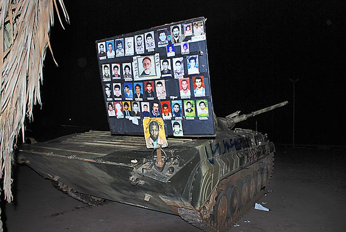 A placard showing photos of some of those who have died is seen on top of a tank, in the early hours of Tuesday, Feb. 22, 2011 in Benghazi, Libya. The bodies of protesters shot to death by forces loyal to Moammar Gadhafi were left on the streets of a restive district in the Libyan capital Tuesday, an opposition activist and a resident said, while the longtime leader defiantly went on state TV to show he was still in charge, though the eruption of turmoil in the capital after a week of protests and bloody clashes in Libya's eastern cities has sharply escalated the challenge to Gadhafi. (AP Photo/Alaguri)