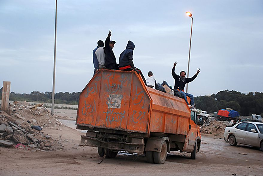 "In this photo taken Monday, Feb. 21, 2011, and made available Tuesday, Feb. 22, 2011, men display victory signs as they ride on a truck scrawled with graffiti in arabic reading ""Go, go, go, leave, leave, leave, down with the regime,"" on their way to volunteer to help clean up streets in Benghazi, Libya. The bodies of protesters shot to death by forces loyal to Moammar Gadhafi were left on the streets of a restive district in the Libyan capital Tuesday, an opposition activist and a resident said, while the longtime leader defiantly went on state TV to show he was still in charge, though the eruption of turmoil in the capital after a week of protests and bloody clashes in Libya's eastern cities has sharply escalated the challenge to Gadhafi. (AP Photo/Alaguri)"