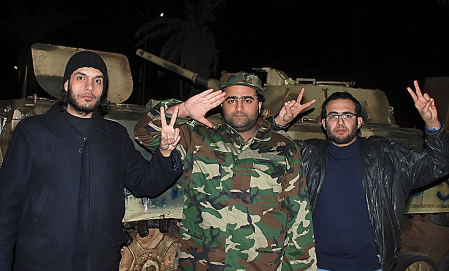 An army soldier and anti-regime residents pose for photos in front of a tank in the early hours of Tuesday, Feb. 22, 2011, in Benghazi, Libya. The bodies of protesters shot to death by forces loyal to Moammar Gadhafi were left on the streets of a restive district in the Libyan capital Tuesday, an opposition activist and a resident said, while the longtime leader defiantly went on state TV to show he was still in charge, though the eruption of turmoil in the capital after a week of protests and bloody clashes in Libya's eastern cities has sharply escalated the challenge to Col. Gadhafi. (AP Photo/Alaguri)