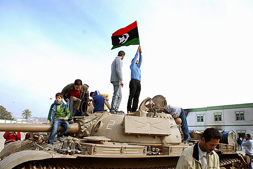 Residents stand on a tank holding a pre-Gadhafi era national flag inside a security forces compound in Benghazi, Libya, on Monday, Feb. 21, 2011. Libyan protesters celebrated in the streets of Benghazi on Monday, claiming control of the country's second largest city after bloody fighting, and anti-government unrest spread to the capital with clashes in Tripoli's main square for the first time. (AP Photo/Alaguri)
