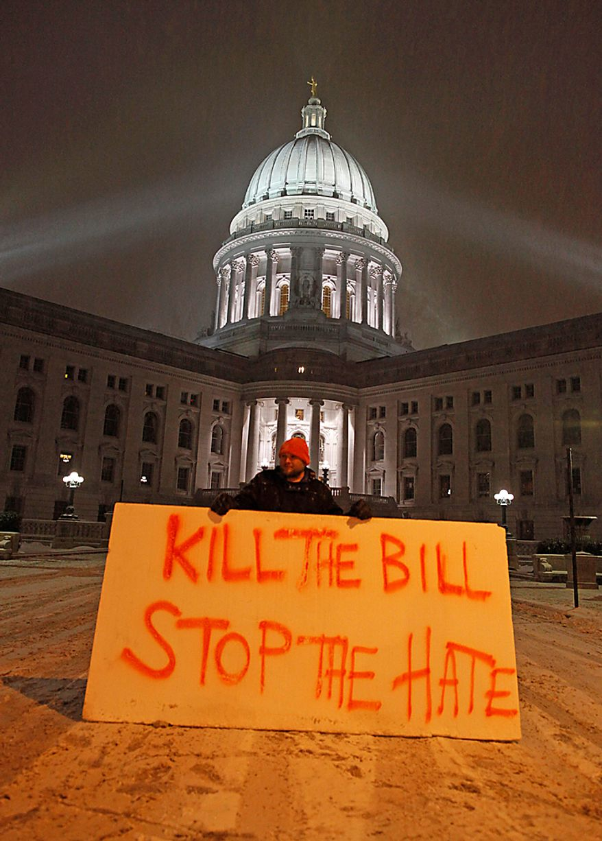 Luke Balsavich holds a large sign outside the state Capitol on Monday, Feb. 21, 2011, in Madison, Wis. Opponents of Gov. Scott Walker's bill to eliminate collective bargaining rights for many state workers are taking part in their seventh day of protests. (AP Photo/Jeffrey Phelps)
