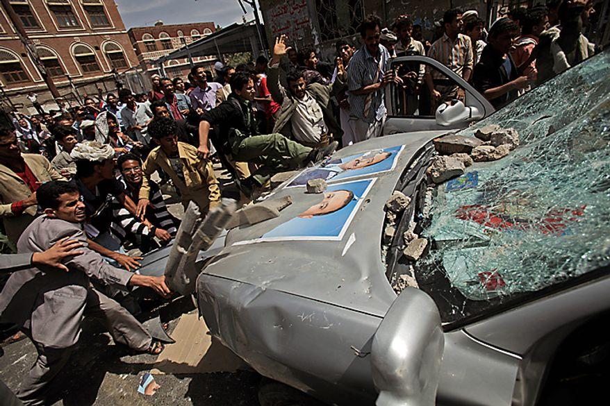Yemeni anti-government demonstrators destroy a vehicle belonging to supporters of President Ali Abdullah Saleh during clashes in Sanaa, Yemen, Tuesday, Feb. 22, 2011. Yemen's embattled leader rejects demands that he step down, calling demonstrations against his regime unacceptable acts of provocation and offers to begin a dialogue with protesters. (AP Photo/Muhammed Muheisen)