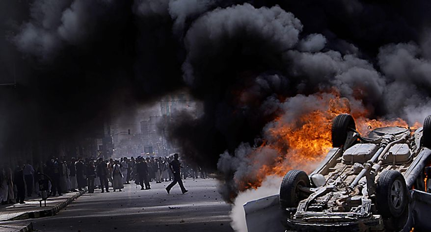 Supporters of the Yemeni government are seen through the smoke of a burning vehicle belonging to them destroyed and set on fire by anti-government demonstrators during clashes in Sanaa, Yemen, Tuesday, Feb. 22, 2011. Yemen's embattled leader rejects demands that he step down, calling demonstrations against his regime unacceptable acts of provocation and offers to begin a dialogue with protesters. (AP Photo/Muhammed Muheisen)