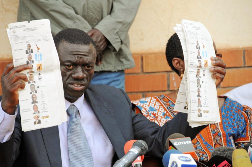 Kizza Besigye, leader of the opposition Forum for Democratic Change, displays pre-marked ballots during a news conference Saturday. He was Mr. Museveni's closest rival, winning about 22 percent of the votes. (Associated Press)