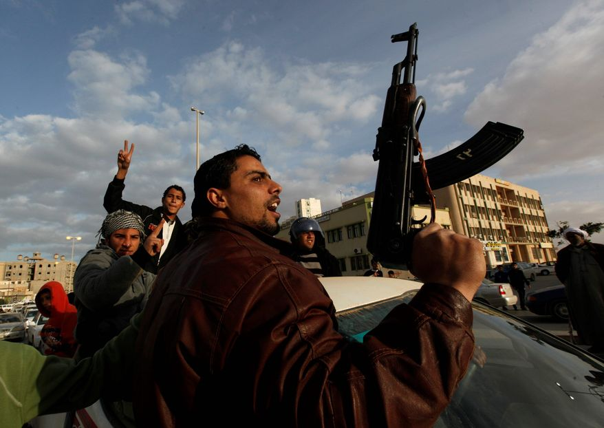 A protester Wednesday shouts slogans against dictator Moammar Gadhafi in Tobruk, Libya. Thousands in the coastal town celebrated their struggle against Col. Gadhafi by waving flags of the old monarchy and firing guns in the air. (Associated Press)
