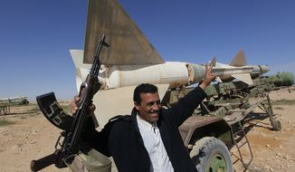 A Libyan popular defence committee member, holds his AK-47 as he flashes V sign in front an anti-aircraft missile at an abandoned Libyan military base near Tobruk, Libya, on Wednesday, Feb.23, 2011. Heavy gunfire broke out in Tripoli as forces loyal to Moammar Gadhafi tightened their grip on the Libyan capital while anti-government protesters claimed control of many cities elsewhere and top government officials and diplomats turn against the longtime leader. (AP Photo/Hussein Malla)