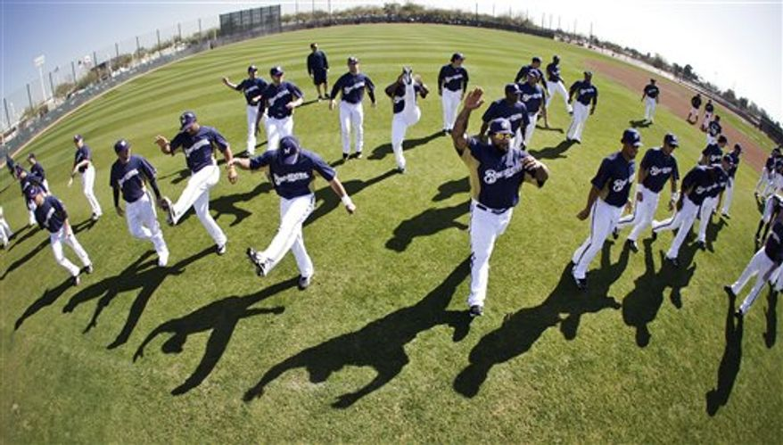 In this image made with a slow shutter, Milwaukee Brewers players, from right, Ryan Braun, Rickie Weeks and Craig Counsell run during baseball spring training, Tuesday, Feb. 22, 2011, in Phoenix. (AP Photo/Morry Gash)