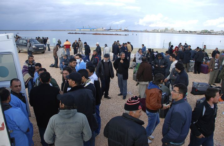 Hundreds of Turkish workers wait to be evacuated from the port of Benghazi in eastern Libya on Tuesday, Feb. 22, 2011. Governments scrambled by air and sea to pick up their citizens stranded by Libya's bloody unrest, with thousands of Turks crowding into a stadium to await evacuation and Egyptians gathering at the border to escape the chaos. (AP Photo/Alaguri)