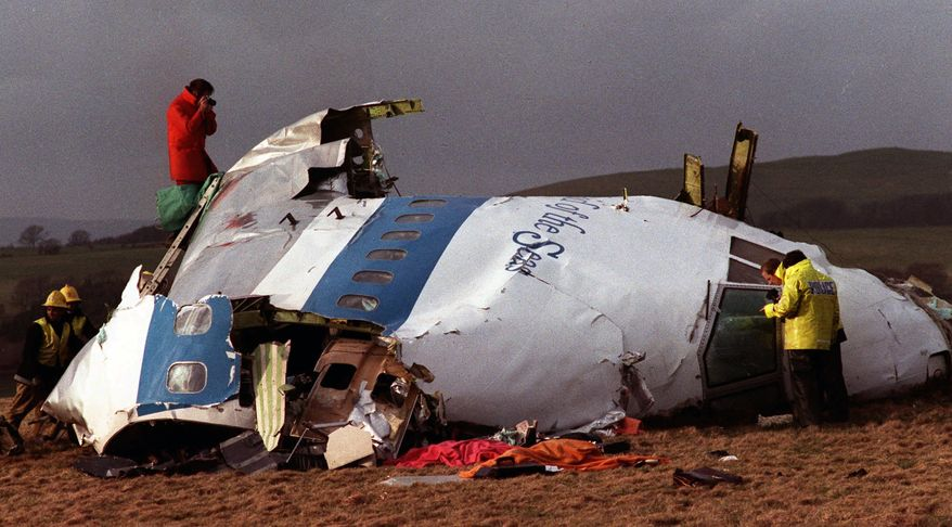 Police and investigators examine what remains of the flight deck of Pan Am Flight 103 on a field in Lockerbie, Scotland, on Dec. 22, 1988. (AP Photo/File)