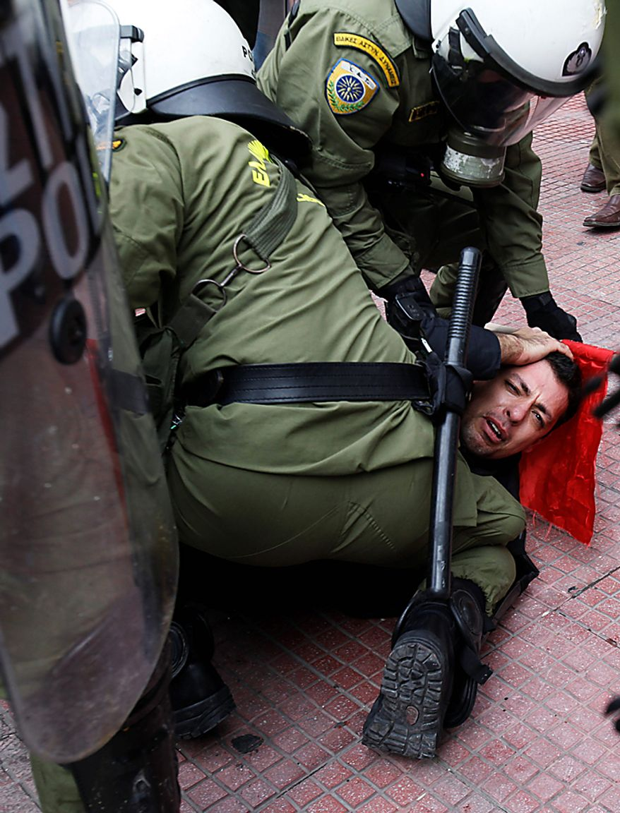 Riot police detain a protester during clashes in Athens on Wednesday, Feb. 23, 2011. Scores of youths hurled rocks and petrol bombs at riot police after clashes broke out during a mass rally taking place as part of a general strike. (AP Photo/Kostas Tsironis)