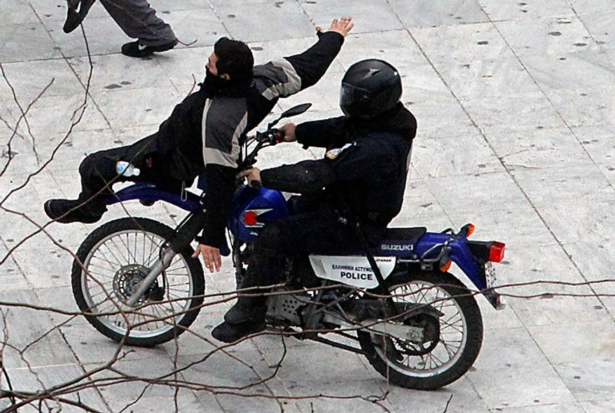 A motorcycle policeman hits a demonstrator during a protest in Athens on Wednesday, Feb. 23, 2011. Scores of youths hurled rocks and petrol bombs at riot police after clashes broke out during a mass rally taking place as part of a general strike. (AP Photo/ Dimitri Messinis)