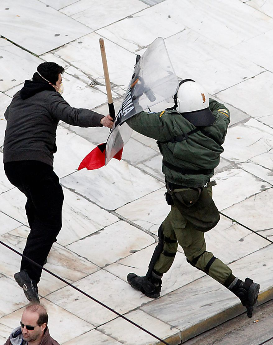 A riot policeman fights with a demonstrator during a protest in Athens on Wednesday, Feb. 23, 2011. Scores of youths hurled rocks and petrol bombs at riot police after clashes broke out during a mass rally taking place as part of a general strike. (AP Photo/Dimitri Messinis)