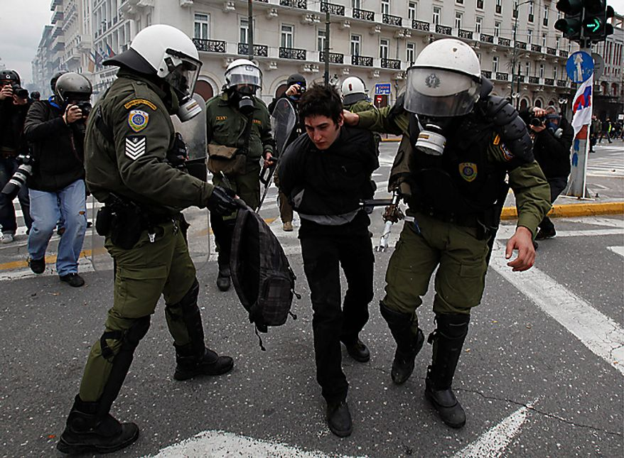 A riot policeman (right) detains a protester while another (left) holds a bag from which an arrow protrudes during clashes in Athens on Wednesday, Feb. 23, 2011. Scores of youths hurled rocks and gasoline bombs at riot police after clashes broke out during a mass rally taking place as part of a general strike. (AP Photo/Kostas Tsironis)