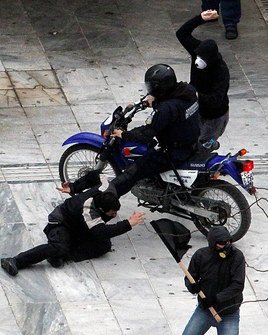 A motorcycle policeman hits a demonstrator with his bike as another protester tries to hit the officer with a stone during a protest in Athens on Wednesday, Feb. 23, 2011. Scores of youths hurled rocks and Molotov cocktails at riot police after clashes broke out during a mass rally taking place as part of a general strike. (AP Photo/Dimitri Messinis)
