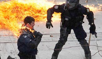 A motorcycle policeman burns as his colleague (right) tries to help him after protesters threw a gasoline bomb in Athens on Wednesday, Feb. 23, 2011. Scores of youths hurled rocks and Molotov cocktails at riot police after clashes broke out during a mass rally that was part of a general strike. (AP Photo/Dimitri Messinis)