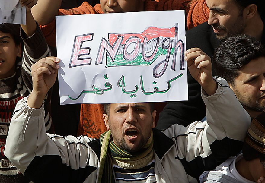 A Libyan protester holds up a sign against Libyan Leader Moammar Gadhafi during a demonstration, in Tobruk, Libya, Wednesday Feb. 23, 2011. Heavy gunfire broke out in Tripoli as forces loyal to Gadhafi tightened their grip on the Libyan capital while anti-government protesters claimed control of many cities elsewhere and top government officials and diplomats turn against the longtime leader. (AP Photo/Hussein Malla)