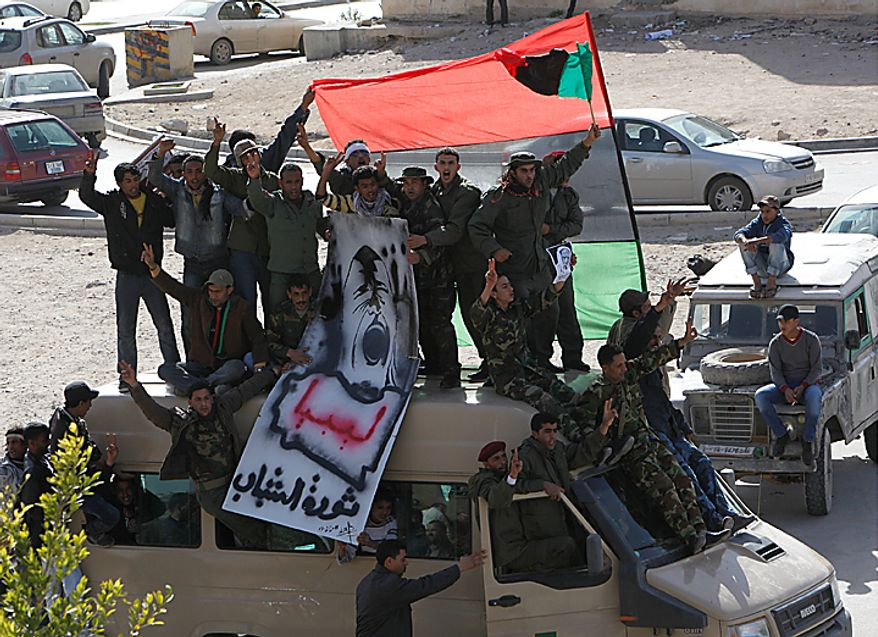 """Libyan army soldiers and other protesters stand over an army van shouting slogans against Libyan Leader Moammar Gadhafi during a demonstration, in Tobruk, Libya, on Wednesday Feb. 23, 2011. Heavy gunfire broke out in Tripoli as forces loyal to Moammar Gadhafi tightened their grip on the Libyan capital while anti-government protesters claimed control of many cities elsewhere and top government officials and diplomats turn against the longtime leader.The writting in Arabic read """"Libya, youth revolution """"(AP Photo/Hussein Malla)"""