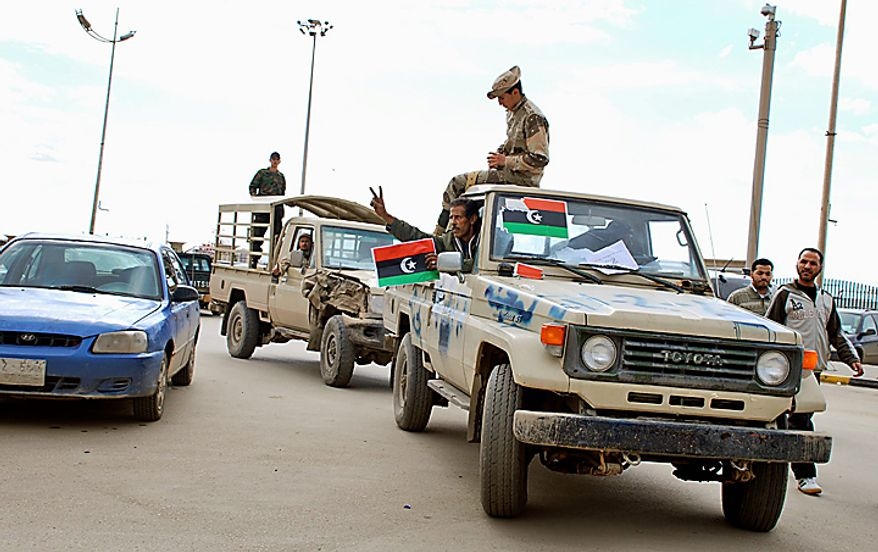 Security forces who have joined the uprising carry the flag of Libya's monarchy, as they drive through Benghazi, Libya Wednesday, Feb. 23, 2011. (AP Photo/Alaguri)