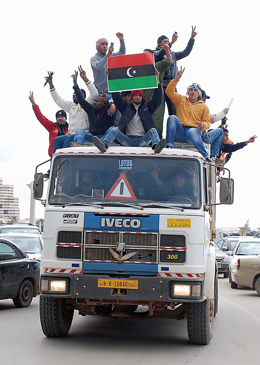 Volunteer residents carrying the flag of Libya's monarchy prior to Moammar Gadhafi's reign, and offering to help in providing municipal services such as cleaning, ride on a truck in Benghazi, Libya Wednesday, Feb. 23, 2011. (AP Photo/Alaguri)