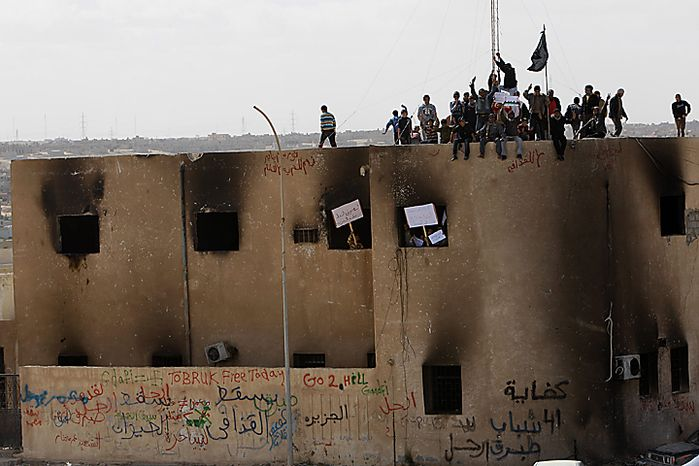 Libyan protesters stand on the rooftop of a burned police station, during a demonstration against their Libyan Leader Moammar Gadhafi, in Tobruk, Libya, Wednesday Feb. 23, 2011. Heavy gunfire broke out in Tripoli as forces loyal to Gadhafi tightened their grip on the Libyan capital while anti-government protesters claimed control of many cities elsewhere and top government officials and diplomats turn against the longtime leader. (AP Photo/Hussein Malla)