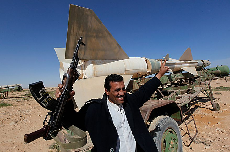 A Libyan popular defence committee, holds his AK-47 as he flashes V sign in front an anti-aircraft missile at an abandoned Libyan military base near Tobruk, Libya, on Wednesday, Feb.23, 2011.  Heavy gunfire broke out in Tripoli as forces loyal to Moammar Gadhafi tightened their grip on the Libyan capital while anti-government protesters claimed control of many cities elsewhere and top government officials and diplomats turn against the longtime leader. (AP Photo/Hussein Malla)