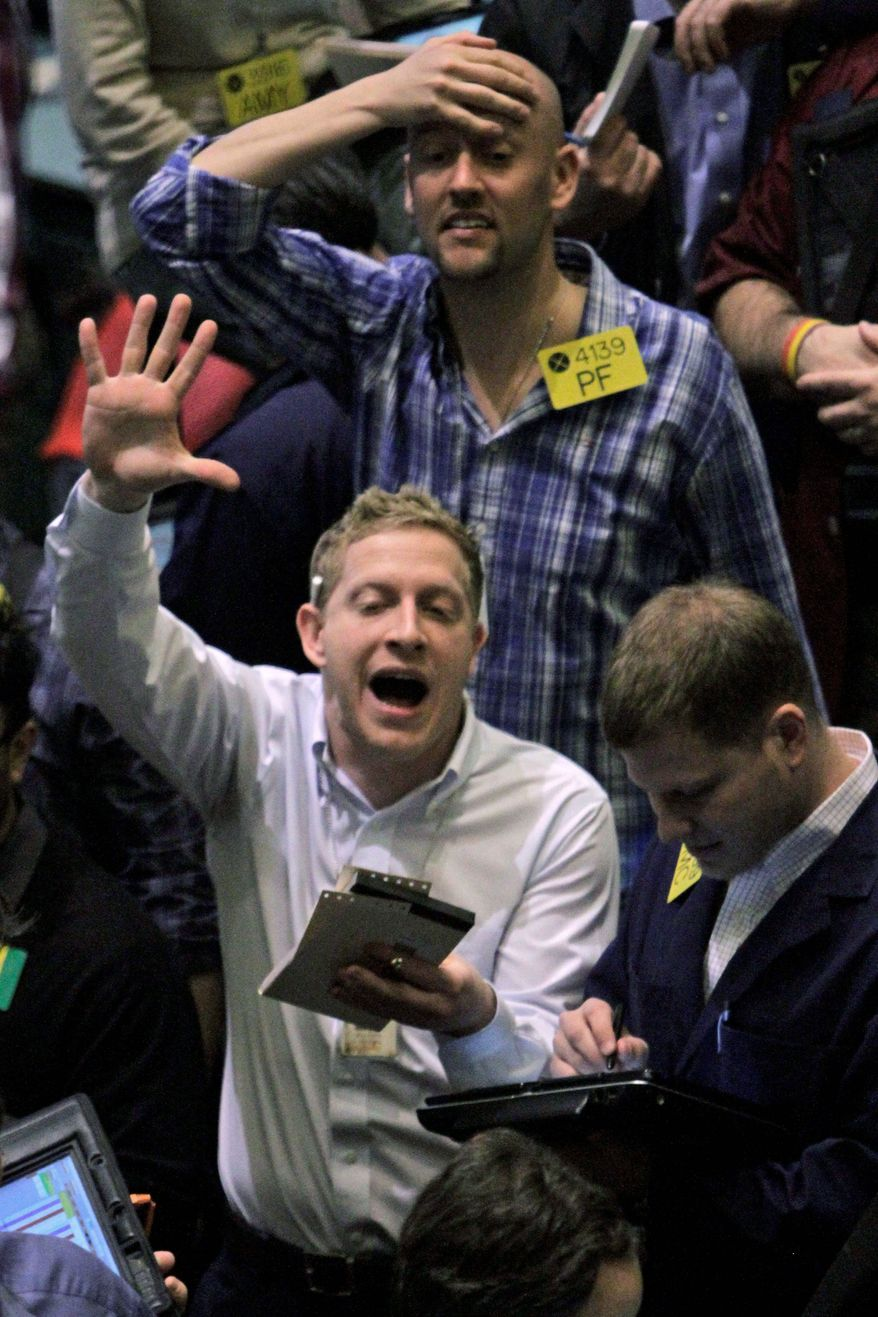 Traders work the crude oil options pit at the New York Mercantile Exchange on Thursday as unrest in Libya sent prices up to nearly $100 a barrel. Traders are worried that revolt could spread to other countries in the Middle East, such as petroleum-rich Saudi Arabia. (Associated Press)