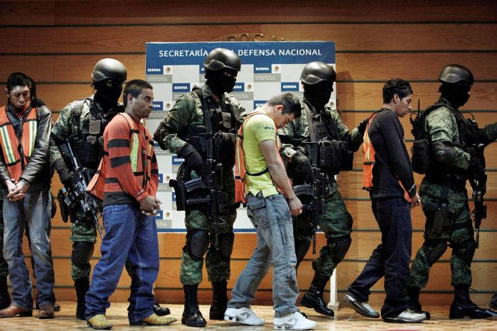 """Soldiers escort Julian Zapata Espinosa (fourth right), also known as """"El Piolin,"""" identified as a member of the Los Zetas drug cartel and the main suspect in the killing of U.S. Immigration and Customs Agent Jaime Zapata. Jesus Ivan Quesada Pena (left), Mario Dominguez Realeo, Domingo Diaz Rosas (third left) and Honduras' citizen Ruben Dario Venegas are also escorted during a presentation for the media in Mexico City on Wednesday. Agent Zapata and fellow agent Victor Avila were attacked Feb. 15 when traveling along a highway in Mexico's San Luis Potosi state. Agent Avila survived the attack. (Associated Press)"""