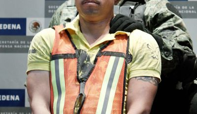 'TWEETY BIRD' DETAINED: A soldier escorts Julian Zapata Espinoza in Mexico City on Wednesday. (Associated Press)