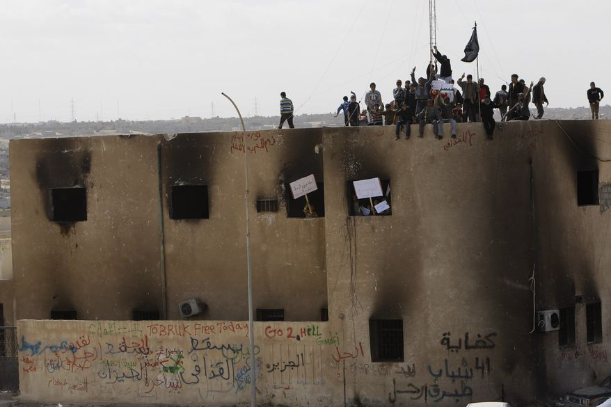 Libyan protesters stand on the rooftop of a burned police station during a demonstration against Moammar Gadhafi in Tobruk, Libya, on Wednesday, Feb. 23, 2011. Heavy gunfire broke out in Tripoli as forces loyal to Col. Gadhafi tightened their grip on the Libyan capital while anti-government protesters claimed control of many cities elsewhere and top government officials and diplomats turn against the longtime leader. (AP Photo/Hussein Malla)