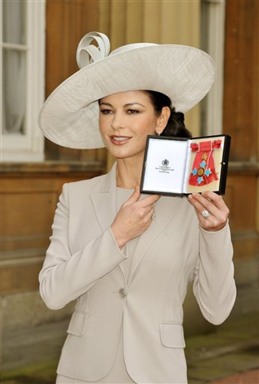 Actress Catherine Zeta Jones displays the insignia after she was made a Commander of the British Empire (CBE) by Britain's Prince Charles at an investiture at Buckingham Palace in London, Thursday Feb. 24, 2011. The 41-year-old Welsh actress who became an Oscar-winning star received the honour for services to the film industry and to charity. (AP Photo/John Stillwell, pool)